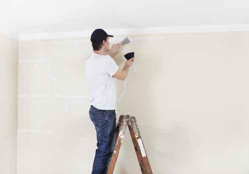 Mann auf Leiter spachtelt Wand